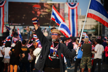 BANGKOK - JAN 25: Unidentified old protester with dress decorations raises Thai flag to anti government at Ladprao street on January 25, 2014 in Bangkok Thailand.