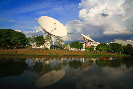 Large broadcast radars, satellite dishes, or radio telescopes with reflection on pond against blue sky photo