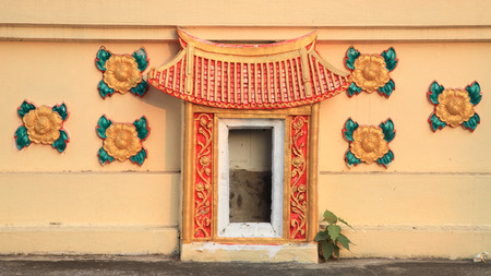 Chinese traditional religion gate symbol decoration on Thai temple wall photo
