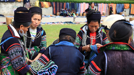 SAPA, VIETNAM - JULY 22, 2012: Unidentified Black Hmongs women with traditional textile from Cat Cat village together at Sapa city. Many Cat Cat tribes walk about 1 mile to Sapa to sell souvenir.