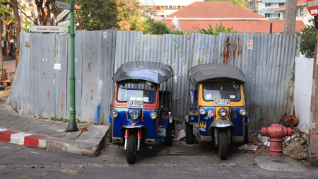 mototaxi: BANGKOK, THAILAND - MARCH 8,2014: Tuk-tuk moto taxi parking on the street to wait passengers. Famous bangkok moto-taxi called tuk-tuk is a landmark of the city and popular transport.