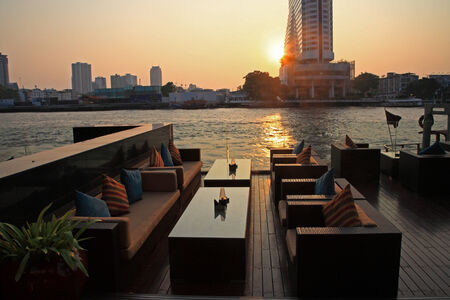 riverside restaurant seats and tables near Chao phraya river during sunset in Bangkok, Thailand