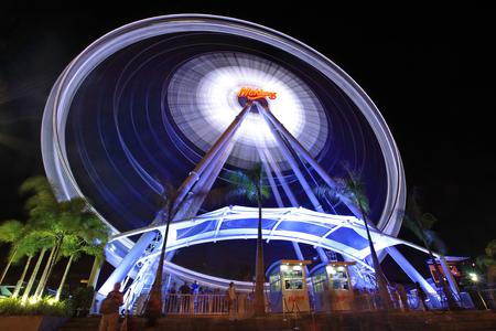 riverfront: BANGKOK, THAILAND - MARCH 8, 2014: Big Ferris Wheel swirling at night in Asiatique The Riverfront. Over 500 fashion boutiques housed in Factory District of Asiatique The Riverfront.