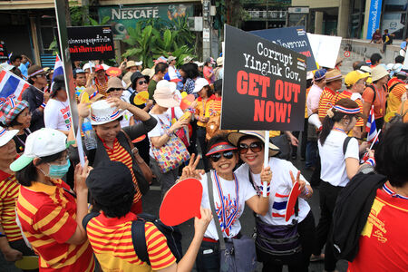 nationalist: BANGKOK, THAILAND-MARCH 29, 2014: Unidentified Thai protestors raisng get out Yingluck banner. More than million people rally around Bangkok streets today.
