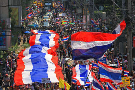 BANGKOK, THAILAND-MARCH 29, 2014: Thai protestors rally with large thai flag from Lumpini park to King Rama 5 statue by 9 km. distance. More than million people rally around Bangkok street today.
