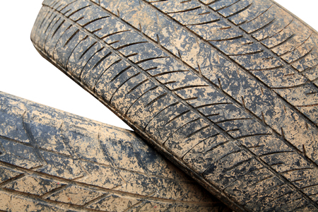 Stack of grunge car tire with brown dirt isolated on white photo