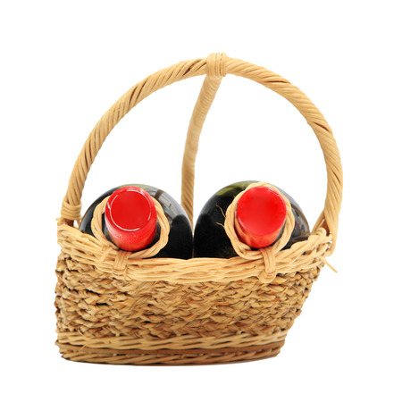 Two wine bottles on present basket isolated on white  photo