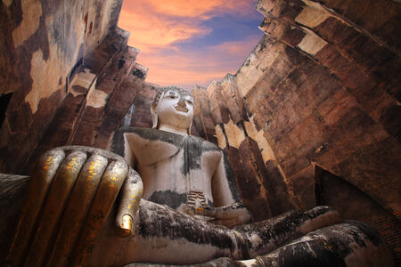 Sukhothai Historical Park: Ancient buddha statue against twilight sky at dusk, Thailand photo