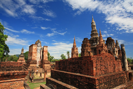 Sukhothai historical park Buddha statue and ancient temple against blue sky at wat Mahathat, Thailand photo