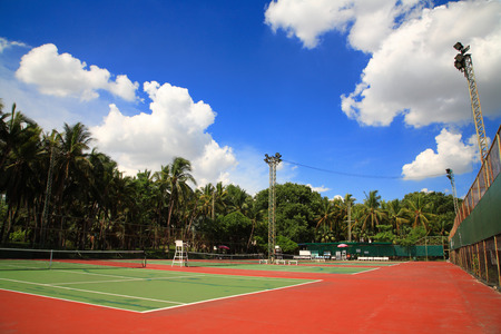 Outdoor tennis courts against blue sky and white cloud