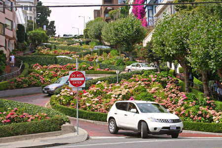 SAN FRANCISCO, USA - AUGUST 28, 2006: Many vehicles drive downhill on Lombard Street, one of the most famous landmark and the crookedest street in the world.