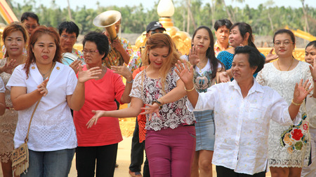 granting: CHACHOENGSAO, THAILAND - JUNE 28 2014: Unidentified people dance and walk before granting Buddha statue to Wat Pak Nam. Traditional culture requires 3 round trips walk and get into temple.