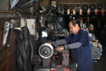 disassembly: BANGKOK, THAILAND - OCTOBER 26, 2013: Unidentified car mechanic fixing disc brake by mechanic machine in the garage. Editorial