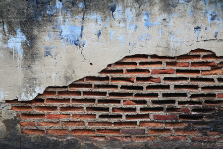 old brick wall with cracked cement by textured background photo