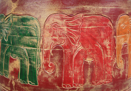 Scrupture of colorful elephants on wooden wall photo