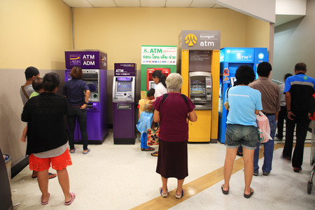 BANGKOK, THAILAND - AUGUST 02, 2014: Unidentified people queuing to withdraw cash in ATM machine. Queue to use ATM is really dense for the beginning of each month. Editorial
