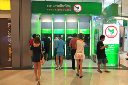 BANGKOK, THAILAND - AUGUST 02, 2014: Unidentified people withdraw cash in ATM of Kasikornbank. Kasikornbank is the 3rd largest Thai banking found on 1945. Editorial