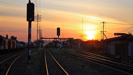 Railway Tracks at Train Station at sunset and twilight sky photo