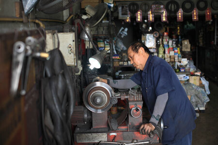 BANGKOK, THAILAND - OCTOBER 26, 2013: Unidentified auto mechanic fixing disc brake by mechanic machine in the garage.