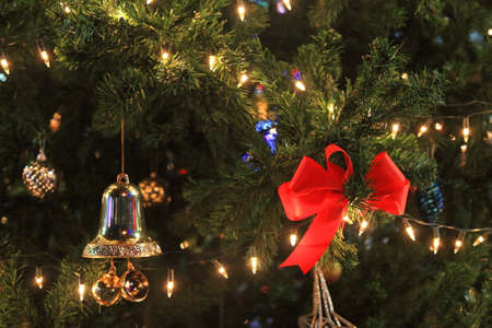 Red bow and bell decorated on christmas tree with light at night photo