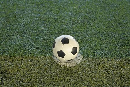 kickoff: Soccer ball at kick-off spot on fake grass soccer field