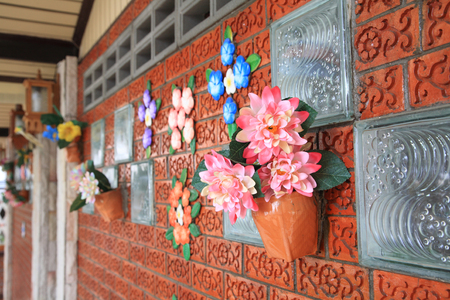 Artificial flowers in pots decorate on brick wall photo