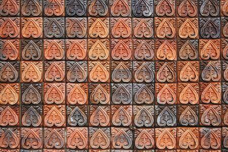 Mur de briques avec motif de feuille floral sculpté