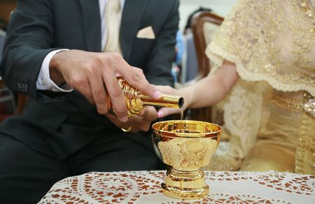 ceremonial: Bride and grooms hands pouring ceremonial water for Thai traditional engagement