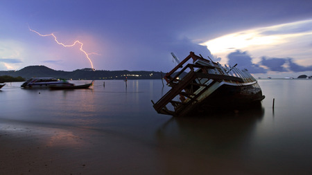 shipwreck and Lightning over sea at dawn in Phuket. Thailand Stock Photo