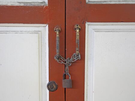 master key: Wooden door locked by master key and iron chain