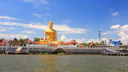 chao praya: Golden Big Buddha statue with reflection of  Chao praya River at Wat Bangchak in Nonthaburi, Thailand Stock Photo
