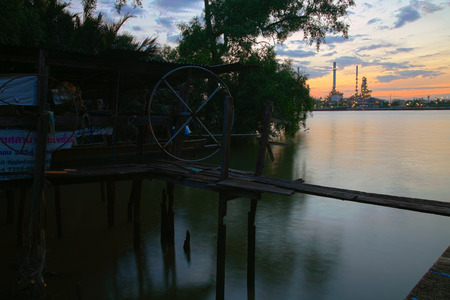 docking: SAMUT PRAKAN, THAILAND - JULY 05, 2015: Wooden motor boat hanging on traditional thai wooden dock opposite with Bangchak Oil Refinery of Chao Phraya river at dawn.