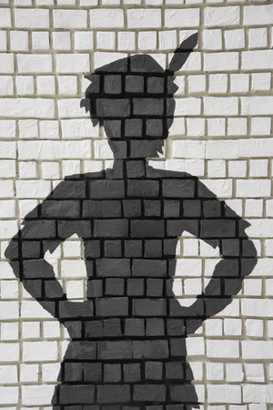 Painted silhouette Peter Pan on white brick wall