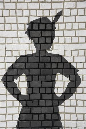 Painted silhouet van Peter Pan op witte bakstenen muur Stockfoto