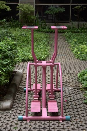 lean machine: Pink exercise equipment in public park, healthy lifestyle