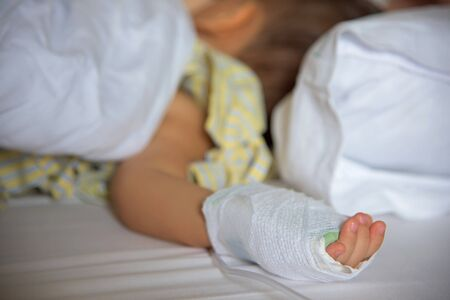 female catheter: Sick Little boy hand with saline intravenous (iv) in hospital bed Stock Photo