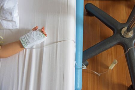 female catheter: hand with saline intravenous (iv) in hospital child bed Stock Photo