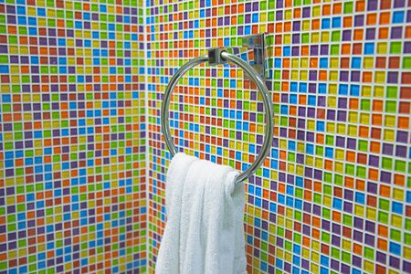 hand towel: hand towel hanging on chrome towel ring at ceramic glass colorful tiles mosaic