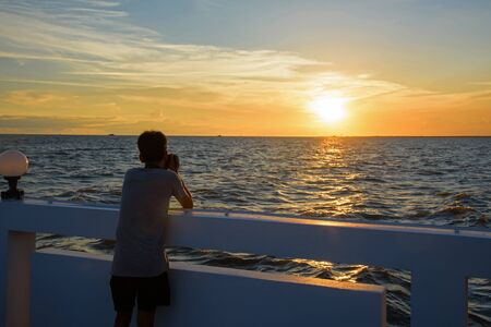 pu: Photographer shooting picture of sunset above sea at Bang pu in Samut Prakan, Thailand Stock Photo