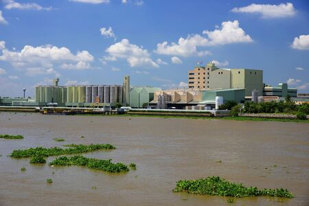 bottleneck: PATHUM THANI, THAILAND - SEPTEMBER 26, 2015: Beer producing factory along Chao Pra Ya river : Singha - The only brewery permitted to display the royal Garuda on the bottleneck.