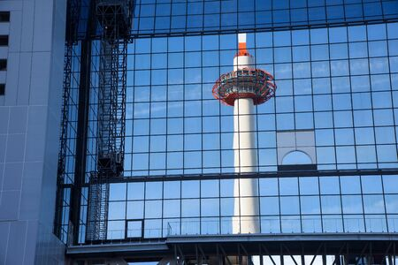 bigger picture: Kyoto Tower mirrored by glass steel of Kyoto railway station, Japan