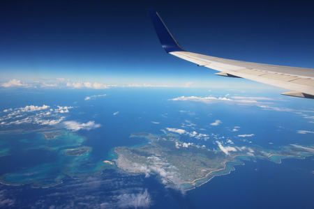 airfoil: Wing of airplane above many islands from window