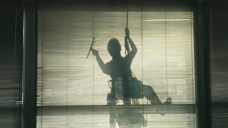 urban: Dangerous working man on high Tower to clean windows, Silhouette scene