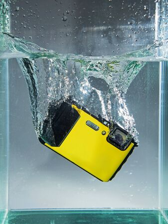waterproof digital camera dropped in container water with splash