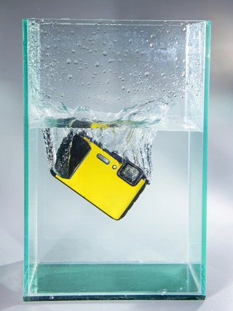 waterproof compact camera dropped in container water with splash