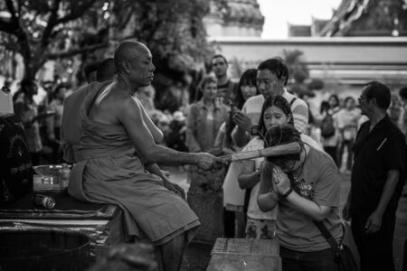 auspiciousness: BANGKOK, THAILAND - JANUARY 01, 2016: Unidentified Thai monk give holy water to people to celebrate 1st day of year 2016 at Wat Pho. Wat Pho is famous on big Reclining Buddha statue inside temple. Editorial