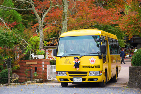 KYOTO, JAPAN - NOVEMBER 13, 2015: Unidentified children in cute school bus on the way the send students back from school.