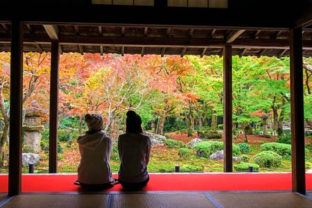 temple tank: Japanese girls enjoy Autumn colorful Japanese garden at Enkoji temple in Kyoto, Japan. Here is the Rinzai Zen Sect and very famous during fall colors in Autumn. Editorial