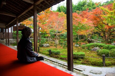 temple tank: Old Japanese woman in Enkoji temple enjoys Autumn colorful Japanese garden in Kyoto, Japan.