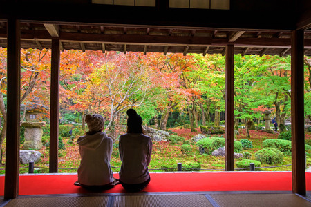 temple tank: Japanese girls in Enkoji temple enjoy Autumn colorful Japanese garden in Kyoto, Japan.